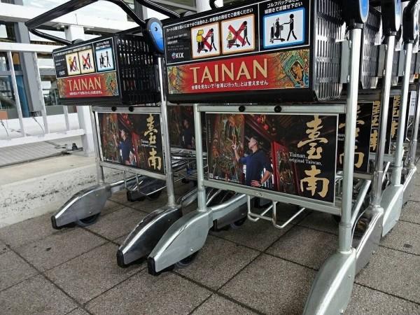 南市觀光旅遊局在日本大阪關西機場行李手推車登廣告,以專業修復師蔡舜任及其所修復的潘麗水寺廟彩繪為主題。(南市觀光旅遊局提供)