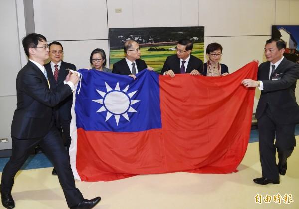 台灣與巴拿馬斷交後,駐巴拿馬大使曹立傑(右三)上月搭機返台,他帶回在巴國所降下的國旗交給前往接機的外交部長李大維(中),並表示「外交人員會繼續努力,為國家的榮譽尊嚴繼續努力」。(資料照,記者朱沛雄攝)