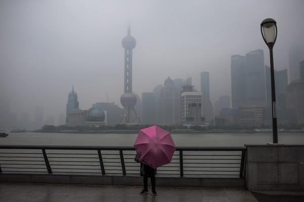 中國共享E傘(Sharing E Umbrella)在短短的幾週時間內,30萬把傘幾乎都不見了。圖為上海民眾撐傘遮雨。(歐新社)