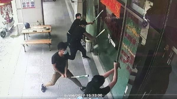 4名黑衣男子持球棒將養生館店面落地窗玻璃砸毀。(記者彭健禮翻攝)
