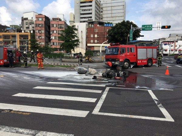 消防隊員撲滅機車的火燒車火勢。(記者周敏鴻翻攝)