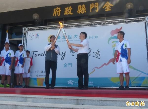 2017世界大學運動會聖火,由台北市副市長鄧家基(右二)手中傳給金門縣副縣長吳成典(右三)。(記者吳正庭攝)