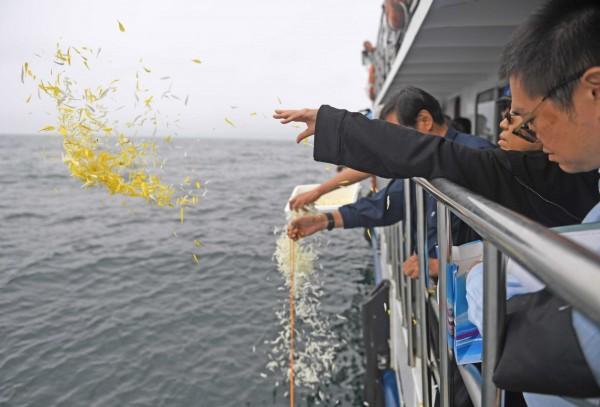 劉曉波於今(15日)中午於進行海葬,家屬把骨灰伴隨著黃色和白色的菊花撒落大海。(歐新社)