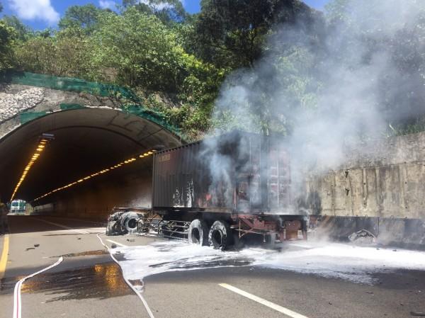 基隆港西岸聯外道路和平隧道前今天下午一輛曳引車後載的40呎貨櫃突然竄出火苗,幸消防隊趕緊滅火,才未波及其他車輛。(記者林嘉東翻攝)