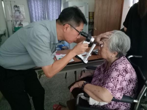義診醫師為阿嬤檢查眼睛。(記者邱灝唐翻攝)