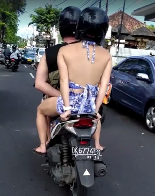 印尼騎士單手騎機車,左手在女孩雙腿間摳摳。(圖擷自Putra Wiyasa臉書)