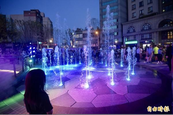 建成圓環中央的乾式噴水池吸引民眾前來玩水。(記者黃耀徵攝)