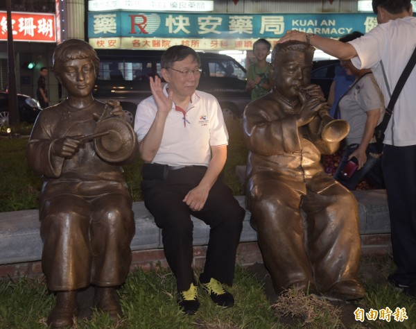 台北市長柯文哲20日出席建成圓環改造完工啟用典禮,並繞行新建綠廣場一圈,和銅像合影。(記者黃耀徵攝)