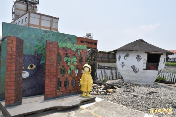 西螺埤頭繪本公園,主角「小美」穿著黃色雨衣站在紅磚牆邊。(記者黃淑莉攝)