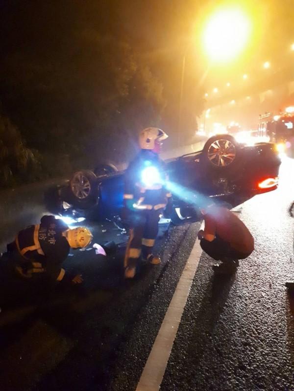 小轎車自撞翻覆,女駕駛受困車內,消防人員趕抵現場救援。(記者曾健銘翻攝)