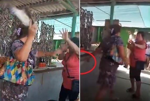 女顧客先以右手拿生魚往老闆臉上打去,被格擋後她迅速「換手持魚」,從更刁鑽的角度發動下一波攻擊。(擷取自YouTube)