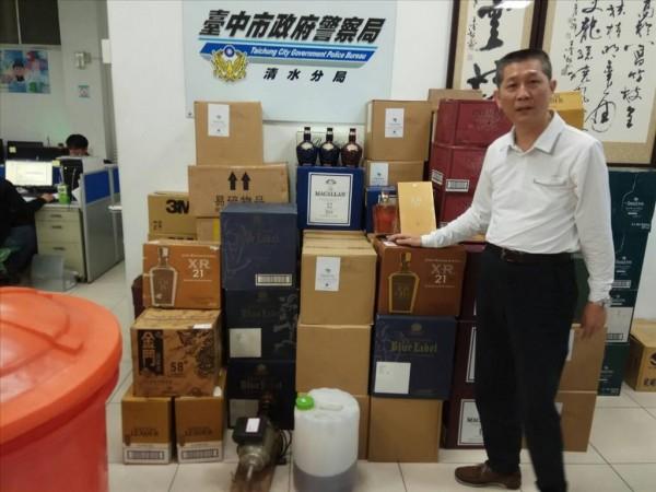 警方當時查獲各類假酒成品,現場為偵查隊長楊錦堂。(記者楊政郡翻攝)