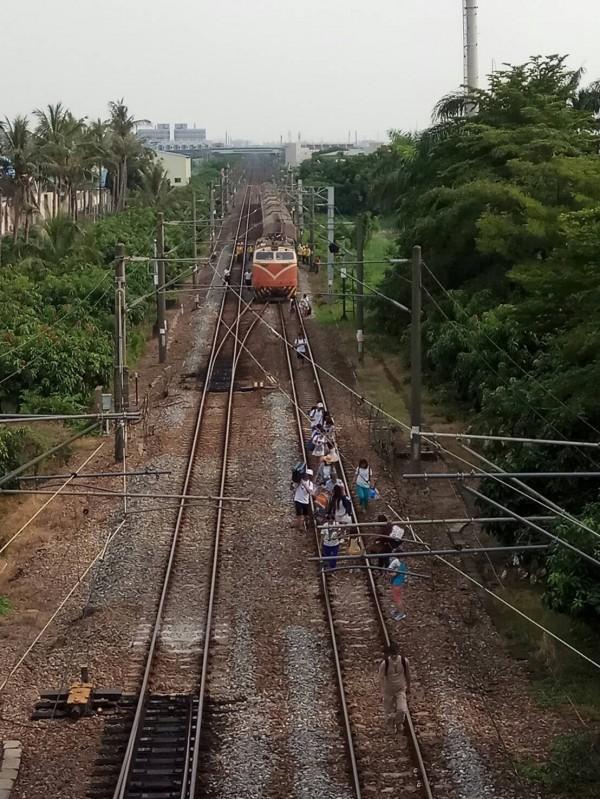 台鐵因號誌故障,導致火車出軌,列車些微傾斜,旅客徒步走回車站,虛驚一場。(記者黃文瑜翻攝)