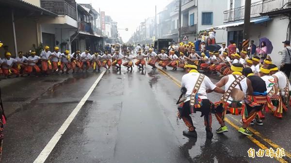 不受尼莎颱風來襲影響,卡大地布勇士們冒雨唱跳傳統歌舞,為部落消災祈福。(記者陳賢義攝)