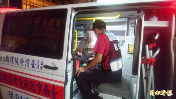 王姓男大生疑似因為受不了被騙,在超商內暈倒,坐進救護車,經過檢查後沒有大礙。(記者王捷攝)