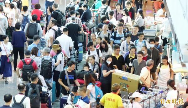 旅客擠滿櫃檯處理後續行程,航空公司和旅客都為這次颱風假挨了一記悶棍。(記者姚介修攝)