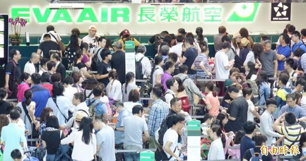 長榮航空因超過500和個空服員臨時無預警請颱風假,造成超過6千名出境旅客行程被迫取消或延誤,旅客擠滿櫃檯處理後續行程。(記者姚介修攝)