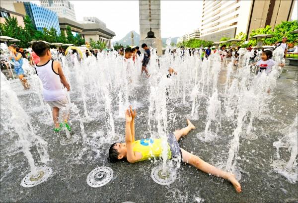 圖為攝氏三十三度以上的熱浪席捲南韓首爾,公共噴泉成為兒童涼快的最佳所在。 (美聯社)