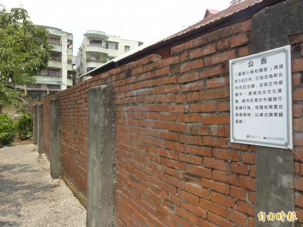 主管機關淡水古蹟博物館在滬尾小學校禮堂外牆張貼出公告,說明該處為文化資產。(記者李雅雯攝)