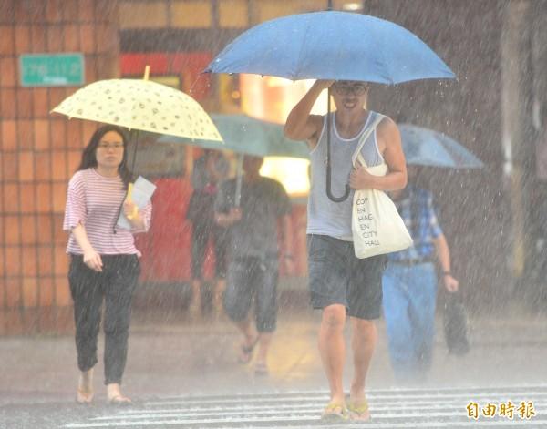氣象局下午發布大雨特報,下午3點5分增強為豪雨特報,午後對流發展旺盛,台北街上下起大雷雨,外出民眾在雨中奔跑。(記者王藝菘攝)