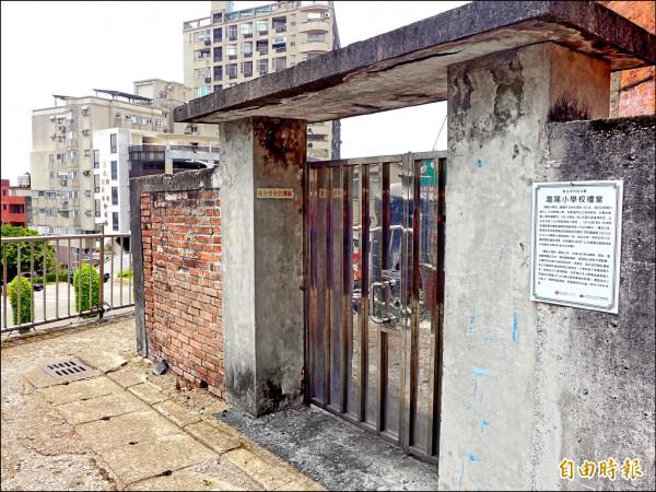 主管機關淡水古蹟博物館在滬尾小學校禮堂外牆張貼公告,說明該處為文化資產。(記者李雅雯攝)