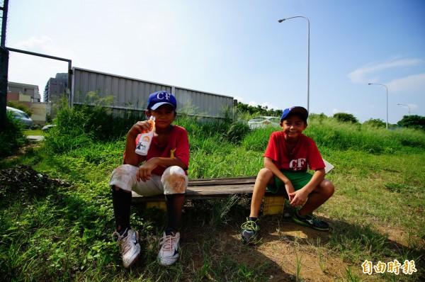 小選手坐在場邊休息,後方雜草叢生。(記者何宗翰攝)