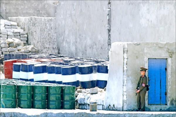聯合國將在五日表決對北韓採取新一輪制裁,禁止北韓出口煤、鐵、鉛和漁產及輸出勞工,削減其全年出口收入十億美元。不過,美國在和中國協商制裁草案時,由於中國反對,因此此次制裁未能納入石油禁運。圖為北韓士兵看守石油桶的檔案照片。(美聯社)