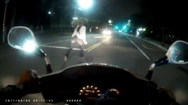 李女突然轉身朝對向車道駛來的汽車,肉身撲車嚇壞所有人。(記者黃良傑翻攝)