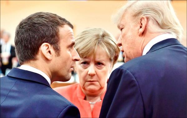 美國總統川普(右)、法國總統馬克宏(左)與德國總理梅克爾(中),七月初在德國漢堡召開的二十國集團(G20)高峰會的首場工作會議開始前交談。(法新社檔案照)