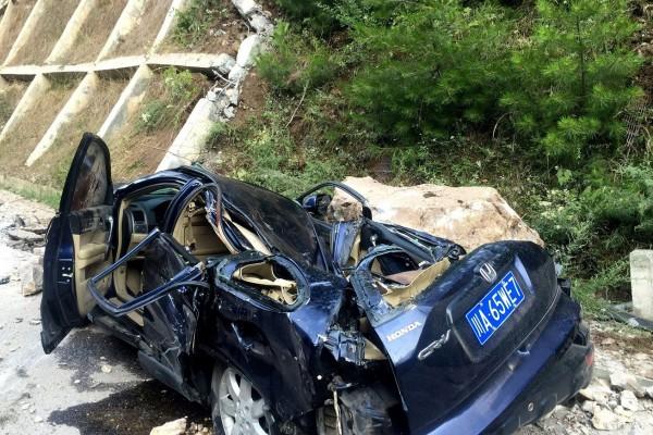 九寨溝地震引發巨石崩落砸毀車輛。(非本文所述轎車,法新社)