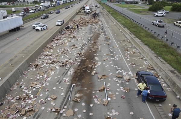 美國阿肯色州30號州際公路,1輛滿載冷凍披薩餅的貨車於9日翻覆,整條馬路變成「披薩路」。(美聯社)
