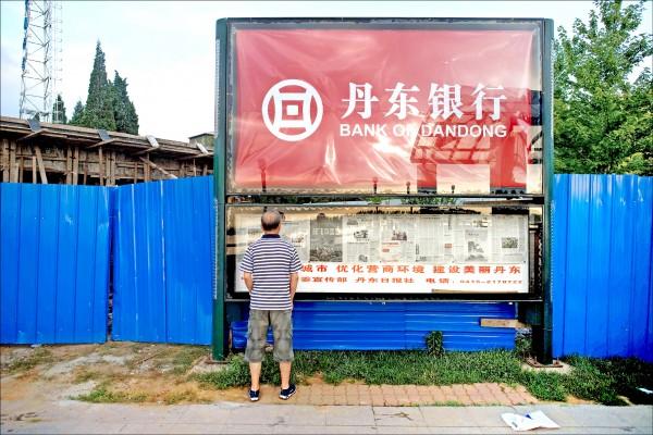 美國若對北韓發動新一波經濟制裁,中國銀行業恐將先被波及。圖為位於中國與北韓邊境處,丹東銀行的廣告看板。(法新社)