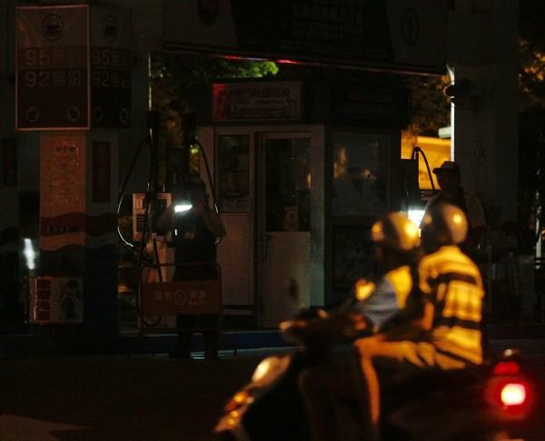 多處加油站停電,員工持手電筒在摸黑的加油站內,向想加油的民眾告知不能加油。(中央社)