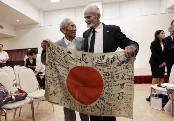斯特魯布(右)在日本將這面旗幟交給安江定男的弟弟。(美聯社)