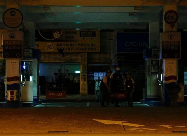 雖然許多地區因停電陷入漆黑,但有加油需求的民眾還是陸續進入停電中的加油站,加油站員工只能摸黑在加油站內提醒民眾暫時無法加油。(中央社)