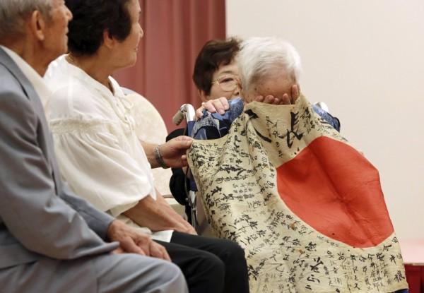 安江定男95歲姐姐含淚收下旗子,稱好像定男真的回到身邊了。(美聯社)