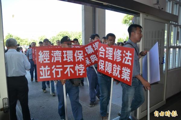亞洲水泥企業工會代表逾40人,一早在經濟部舉辦的花蓮場《礦業法》修法公聽會場外高舉「合理修法、保障就業」等標語。(記者王峻祺攝)