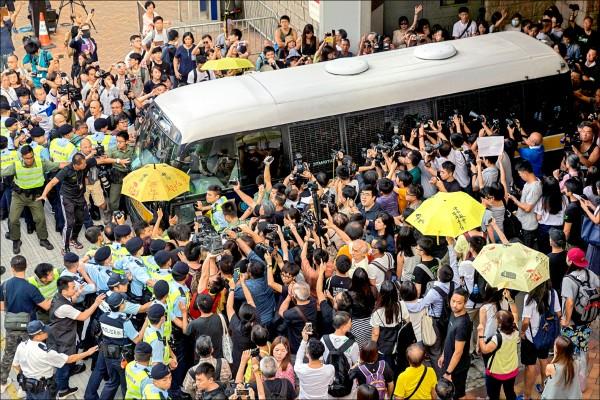 香港「雨傘革命」領袖黃之鋒、周永康、羅冠聰三人,十七日被改判徒刑後,大批支持者包圍據信搭載黃之鋒的囚車加以聲援。(歐新社)