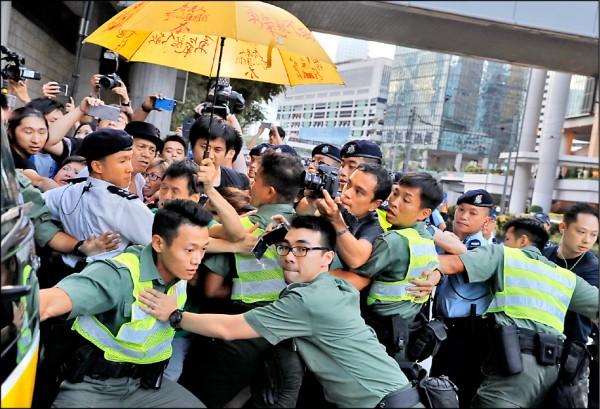 香港「雨傘革命」領袖黃之鋒、周永康、羅冠聰三人,十七日因佔領港府總部廣場行動刑期上訴案被改判徒刑後,前往高等法院聲援的大批支持者情緒激動,高舉象徵雨傘革命的黃色雨傘,包圍據信搭載黃之鋒的囚車,警方奮力為囚車開道。(美聯社)