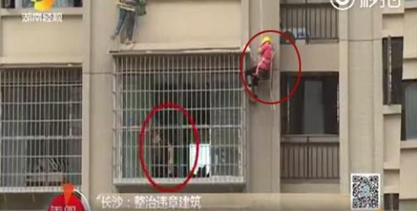 工人在奉命拆除高樓外牆的違建時,身上的安全繩竟遭不滿的屋主砍斷。(擷取自秒拍畫面)
