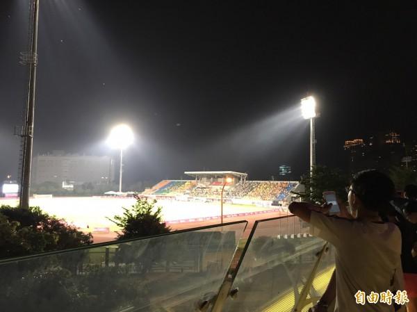昨晚買不到票進場看俄羅斯對上巴西男子足球賽的民眾,站在竹北斜張橋上,對照開賽前20分鐘內的球場觀眾席,顯得諷刺。(記者黃美珠攝)