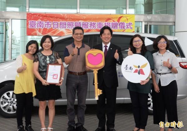 郭福源(左三)由家人陪同捐贈日間照顧服務車一輛給市政府,由市長賴清德(右三)代表受贈。(記者蔡文居攝)
