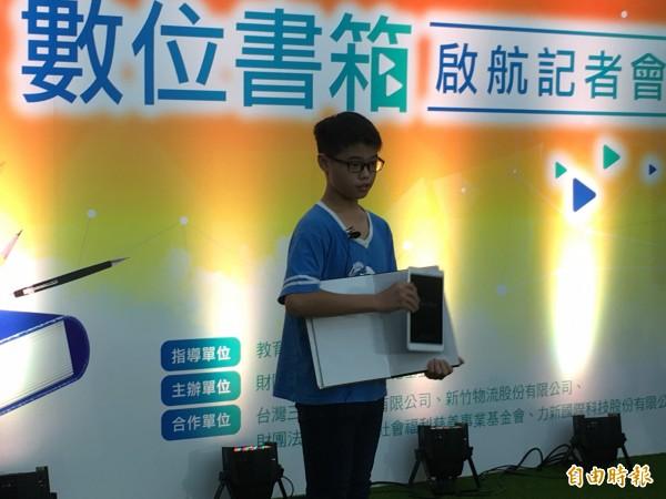 「愛的書庫」數位化,在偏鄉推動數位書箱,今天在教育部舉辦記者會,「小老師」帶來小魔術表演,從平面紙本書中變出數位平板。(記者林曉雲攝)
