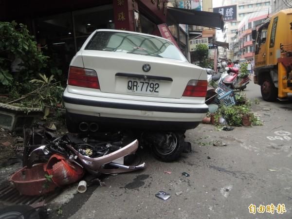 機車被壓在BMW下方。(記者張軒哲攝)