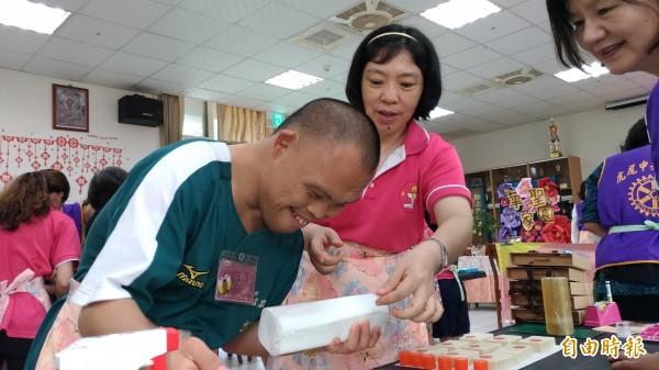 26歲的王彥之(左)有條不紊地教大家製做手工皂,還頻頻謝謝大家買他的香皂。(記者廖淑玲攝)
