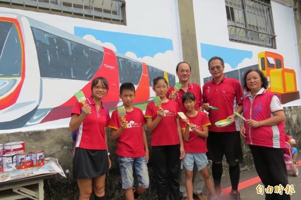 勝安里志工與開元國小師生一起合作,彩繪社區鐵道意象。(記者蔡文居攝)