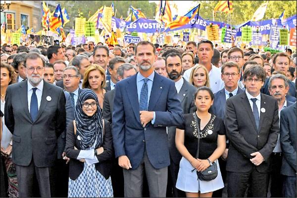 西班牙加泰隆尼亞自治區首府巴塞隆納市中心廿六日湧入五十萬人,高舉代表巴塞隆納的紅、黃、白花束,高呼「我不害怕」,沿著格拉西亞大道(Paseo de Gracia)遊行至加泰隆尼亞廣場(Placa de Catalunya),國王菲利普六世(中)和總理拉霍伊(左一)也現身隊伍。(法新社)