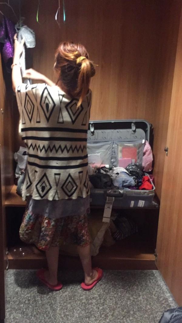 以觀光名義來台賣淫的翟娜,收拾自己的衣物,準備與警方回警所應訊。(記者徐聖倫翻攝)