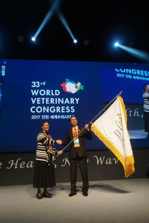 江世明從前任會長、來自美國的René A. Carlson手中接下世界獸醫師會的會旗。(圖由《派特88》寵物資訊網提供)