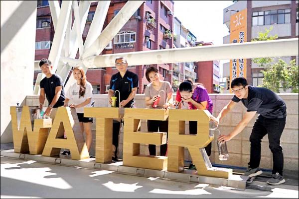 台北田徑場以英文單字「WATER」打造的直飲台,造型吸睛,設計人是北水處工程師林志成(左三)。(北水處提供)